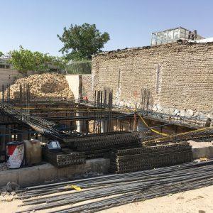 Iranilainen rakennustyömaa, paaluja ja tiiliseinää